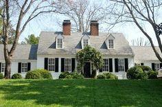 White house, black shutters, vine over the door, dormers, boxwoods
