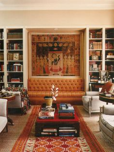 1063  House Beautiful: Decorating with Books; Hueston    A sophisticated library and seating area with a touch of exotic Asian furnishings in warm reds and oranges make this an inviting space. The bookcases with red-painted backs frame a built-in settee (love that fringe) and a low coffee table provides space for displaying handsome volumes both on top and below. Plus a bar cart at right – what else could one ask for?    [Shelving framing a settee instead of a fireplace or a window. One must…