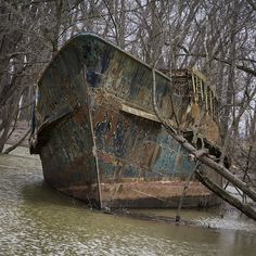 """Ghost Ship"" in a creek near Cincinnati off Ohio river. The ""Circle Line V"" was launched on April 12, 1902 as the ""Celt"" and has had a long and interesting history before being ground in the creek off the final owner's property in 1986. It rots there to this day. More info at: http://queencitydiscovery.blogspot.com/2013/03/the-ghost-ship.html"