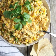 This Creamy Cheesy Corn Dip is sunshine in a bowl! Cheddar cheese, cream cheese, sour cream, jalapeños, and everyone's favorite veggie: CORN! | Taste And See