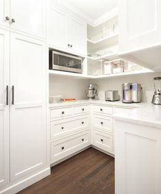 Gorgeous U-shaped kitchen pantry boasts white shakers cabinets fitted with dark nickel hardware and topped with white marble countertops while above the counters open shelving holds a stainless steel microwave and other kitchen essentials.