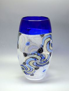 This astounding large vase was made by Michael Hunter for Twists Glass in 2016. It is a very elegant shape that starts with a cobalt blue incalmo top. Sandwiched between the blue in cal on top and the white latticino base is a broad band of large white rondel canes with blue flower murrine centres and blue black and green rondel canes with white rose murrine centres. Closer inspection will reveal that the roundels are laid in a vertical diagonal pattern around the middle section…