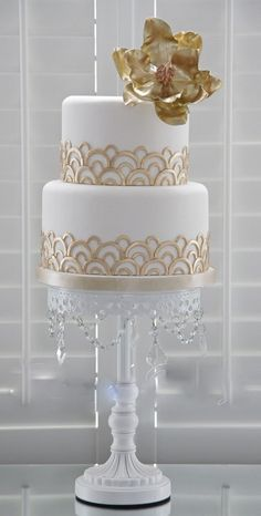 two tier round art deco wedding cake with gold accents and topper