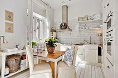 aranżacja białej kuchni,kuchnia w mieszance stylowej scandy i provence,skandynawsko-francuska aranzacja białej kuchni,mix stylowy w białej kuchni,biały stół skandynawski z drewnianym blatem,krzesła w bialych sukienkach,białe ubranka na krzesła,białe drewniane półki wiszace do kuchni,biała płytka cegiełka w kuchni,białe tradycyjne szafki kuchenne w stylu skandynawskim,ceramiczny biały zlewozmywak,biała konsolka w kuchni,wiklinowe kosze,wiklinowe wianki,szafka na wino,metalowe białe pojemniki…