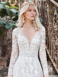Hey pretty lady, it appears you've struck that perfect balance of boho and classic with this romantic illusion sleeve A-line wedding dress. Cheers to your best day ever! Beaded lace motifs over sparkle tulle Sheer organza lined beaded lace bodice Deep illusion V-neckline V-back Long illusion lace sleeves Covered button over zipper closure Extra lace motif included for minor neckline alterations Also available sleeveless (Raphael Dawn) Available in plus size