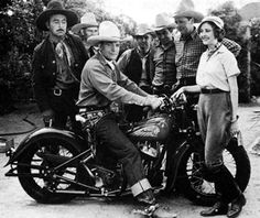 """Buck Jones is mighty proud of his new Indian motorcycle. Standing in front is """"Red Rider"""" serial heroine Marion Shilling. Beside her in the checkered shirt is Ed Cobb. Photo taken in 1934 during the making of that Universal serial. (Photo courtesy Bobby Copeland.)"""