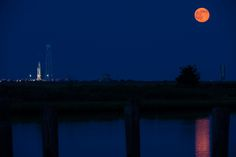 """A dazzling """"supermoon,"""" also known as a full perigee moon, rises in the night sky to the right of an Orbital Sciences Corporation Antares rocket and its Cygnus spacecraft payload on Saturday, July 12, 2014 at Pad-0A of NASA's Wallops Flight Facility on Wallops Island, Virginia."""