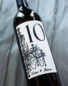 This is a great idea for table numbers - bet the guests have a bit of a tussle over who gets to take it home!  Table Number Wine Labels 1-10... Choose your Color...Damask Chandelier. $20.00, via Etsy.