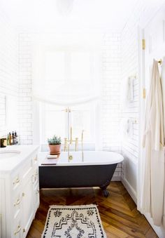 Bright white bathroom with clawfoot bathtub and patterned runner.