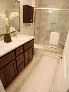 Marble shower walls and a tile-and-marble floor give this bathroom traditional appeal, while a sleek shower wall and contemporary vanity keep the style fresh.
