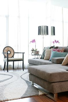 In the living area, the pink and blue prints on the pillows make the gray L-shaped sectional sofa more interesting. On one side of the sofa is an accent chair with a surprising detail: a solihiya back. The space is completed with a floor-to-ceiling mirror behind the sofa that makes the small area seem bigger than it really is.