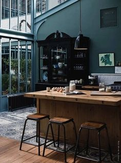 Gorgeous dark industrial kitchen. Love the architecture and the butcher block island.