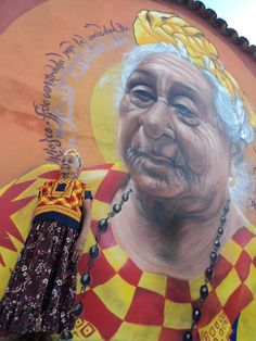 A woman poses in front of a mural of her in Juchitán, Oaxaca, México. Artwork by…