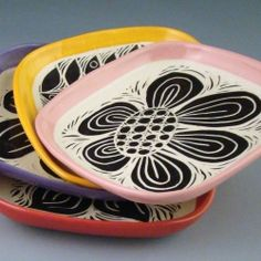 Handmade sgraffito trays with bold black and white designs and a splash of bright color.