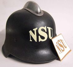 WWII NSU Factory Guard, Air Defence & Fireman's Helmet Stencil During World War II NSU designed and produced the Kettenkrad, the NSU HK101, a half-tracked motorcycle with the engine of the Opel Olympia. It was acquired by Volkswagen Group in 1969. VW merged the company with Auto Union, to eventually evolve into Audi as it is known today. This stencil marking would have been worn on the helmets of NSU employed personnel, air defence, Fire units and Security guards.   www.warhats.com
