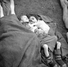 The corpses of two children who succumbed to typhus and starvation wait to be buried following the liberation of Bergen-Belsen concentration camp. When British and Canadian troops entered the camp on 14 April 1945, they found over 13,000 unburied bodies and (including the satellite camps) around 60,000 inmates, most acutely sick and starving
