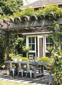 Pergola with vine over dining area. White windows and trim, dark siding, wood pergola, large gray pavers Outdoor Rooms, Outdoor Dining, Outdoor Gardens, Outdoor Decor, Dining Area, Outdoor Tables, Rustic Outdoor, Patio Dining, Rustic Table