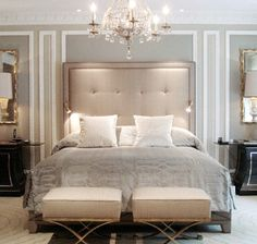 I love the glamorous look of a tall tufted headboard paired with an elegant chandelier.... AND those awesome ottoman/footstools at the end of the bed.