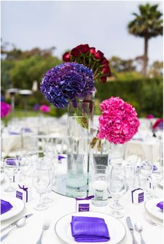 Tall glass cylinder vases with bright purple and pink hydrangea, and red roses | OCLA Events