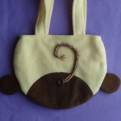 This Winking Monkey Purse, another one of my newest addition to the animal purse collection, is perfect to carry around anytime and will catch many peoples attention.  This purse is made of fleece with cotton blend knit fabric for lining. The handle measures 8 in height and the purse is made with yellow and brown fleece. This winking monkey has two 3D ears and hand stitched eye and mouth with black DMC floss. The back of the purse features the monkey tail made with three different brown…