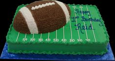 Football 1st Birthday Cake. Green buttercream iced, sheet cake decorated as the football field topped with a football shaped cake. Everything on this cake is edible. (Serves 24-98 party slices.)