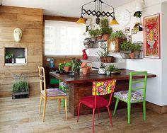 Na varanda gourmet, a horta e a madeira de demolição, que cobre piso e paredes, dão a desejada sensação de se estar numa casa. Os vasos ficam sobre a mesa e em suportes na parede. Projeto do escritório Lovisaro Arquitetura e Design