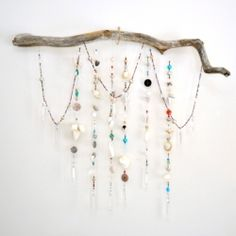 A twisted driftwood branch served as the inspiration for a wall hanging made from beads, seashells and chandelier prisms.