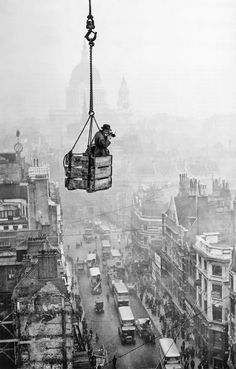 High Flyer, December 1929: Fox photographer and daredevil R J Salmon dangles in a crate suspended from a crane to take an aerial shot of Fleet Street, London. St Paul's Cathedral may be seen in the misty background. This picture is taken from the Daily Telegraph building. (Photo by Fox Photos/Getty Images)