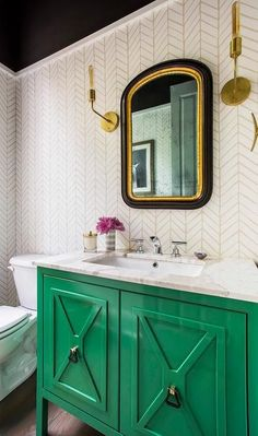 Charming contemporary powder room stands out with an emerald green washstand fitted with a cream marble countertop fitted with a sink and polished nickel faucet fixed beneath a gold and black vanity mirror mounted to a wall clad in Serena & Lily Feather Wallpaper between brass sconces illuminating a black ceiling.