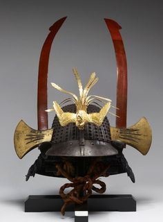 """Samurai War Helmet.  1825-1875, Japan.  This helmet has an iron """"hachi"""" of thirty-three riveted laminations, a """"shikoro"""" of five plates laced in """"kebiki"""" (spread hair) style with navy blue """"ito doshi"""" laces, and axes as """"yokodate"""" made from whale baleen. A Phoenix (""""Ho o"""") serves as a """"maedate;"""" one tail feather is missing. It is lined with rawhide."""