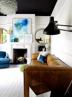 Inspirational interior with white wooden floor, a cozy tan leather couch, massive glass chandelier and blue design details.