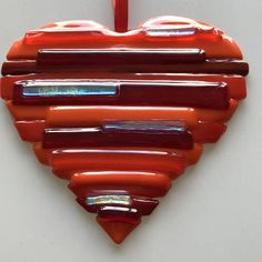 This fused glass heart in various red and orange colors and a few dichroic glass pieces looks beautiful on your wall or as a suncatcher in your window. The item was tack fused at around 1250F so that the stripes of the heart are raised. It makes a beautiful gift for a loved one.