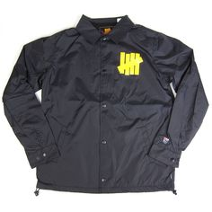 """Undefeated's take on the classic Coach jacket. Features printed 5-strike logo at the chest, Bad Sports logo on the back, hand warmer pockets and """"U"""" embroidery on the wrist. Snap button closure, stand"""