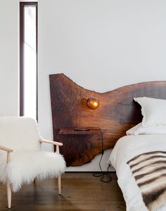 In the master bedroom is a custom-designed Claro walnut bed. A fuzzy Cortina chair from Refuge sits beside a Modo desk lamp by Jason Miller for Roll & Hill. (Photo: Trevor Tondro for The New York Times)