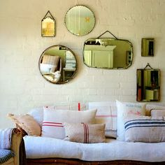 old mirrors grouped on mass and home made linen pillows