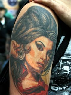 Tattoo of Amy Winehouse on man's arm