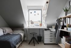 Small grey attic bedroom with workspace