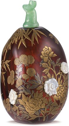 A MOTHER-OF-PEARL EMBELLISHED AMBER SNUFF BOTTLE QING DYNASTY, 18TH / 19TH CENTURY, EMBELLISHED BY TOMIZO SARATANI the egg-form amber bottle of attractive rich mahogany-red colour, delicately embellished in mother-of-pearl and gold lacquer with a continuous design of the 'Three Friends of Winter'