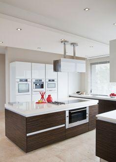 cocina moderna con isla central para zona de cocción, encimera blanca, muebles bajos color wengué, módulo lacado en blanco para electrodomésticos y almacenaje