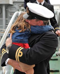 A Royal Navy Officer hugs his daughter after a very long deployment