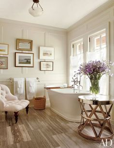Paintings of Long Island are grouped in Susan's bath; the side table is from Homenature, and the tub fittings are by Perrin & Rowe.