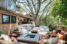 Huge tree surrounded by wood deck, lounging space around fire pit!! LOVE! Mill Valley House by Urrutia Design