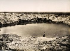 A huge bomb crater at Messines Ridge in Northern France, c. March 1919, soon after the end of the War.