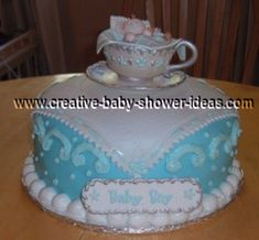 elegant baby boy shower cake with edible tea cup on top with baby sleeping inside