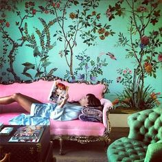 Green floral wallpaper with pink sofa.