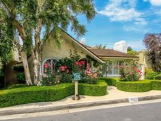 Perfectly-manicured hedges line the way up to this delightful cottage.
