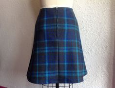 This skirt is made of plaid wool in charcoal gray, blue and turquoise cut in a flattering a-line shape. The right front panel is made out of solid charcoal gray wool. In between the two front panels is a scalloped strip of bright blue wool with black buttons decorating each tab. The skirt is fully lined and zips up the back.  This skirt had a 32 waistband and will fit up to 42 hips so about a size 10 22 long  Hand wash and air dry or dry clean