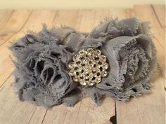 This headband has two gray shabby chic flowers, each measuring about 2.5 inches. They feature a stunning rhinestone embellishment. They are attached