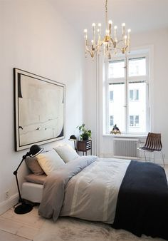 simple bedroom + black floor lamp + gold retro chandelier + painting