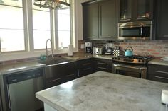 Liking the lighter finish of the stained concrete with charcoal cabinetry.